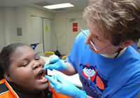 Dr. Carol Haggerty of UFCD Community Based Programs applies fluoride varnish on Micanopy 9th grader Jualenia Foster.
