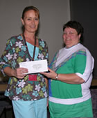 Mary Bennett (r) awards Marilyn Stewart a fat check for getting thinner.